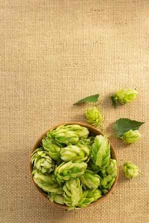 herbaceous border: bowl full of hop cones on burlap sack