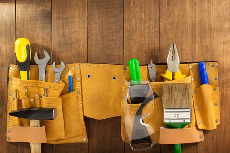 suede belt: tools and instruments in belt on wooden background Stock Photo