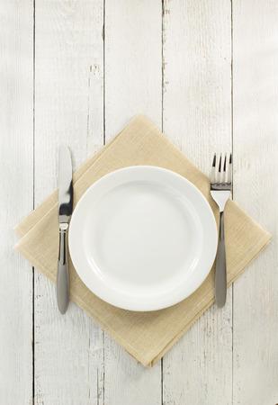 cuchillo: cuchillo y tenedor con el plato en la servilleta sobre fondo de madera