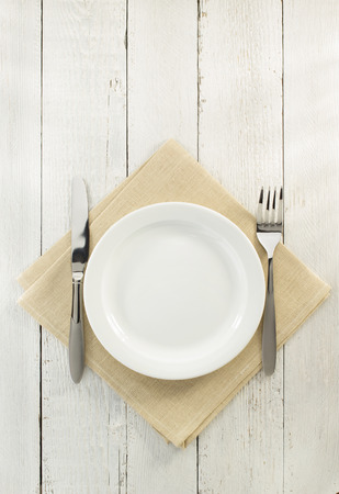 knife and fork with plate at napkin on wooden background Standard-Bild