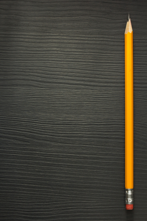 housebuilding: yellow pencil on wooden texture