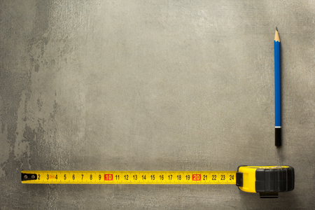 housebuilding: tape measure and pencil on old texture Stock Photo