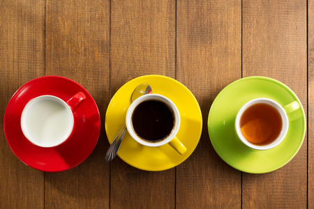 red tea: cup of tea, milk, coffee on wooden background