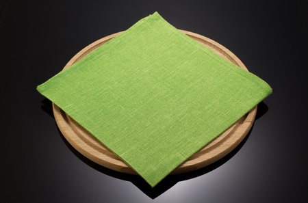 black dish: napkin cloth and cutting board on black background