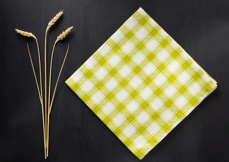ear checked: ears of wheat and cloth  on wooden background