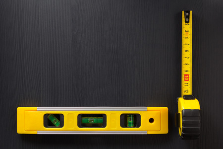 housebuilding: tape measure and level on wooden texture