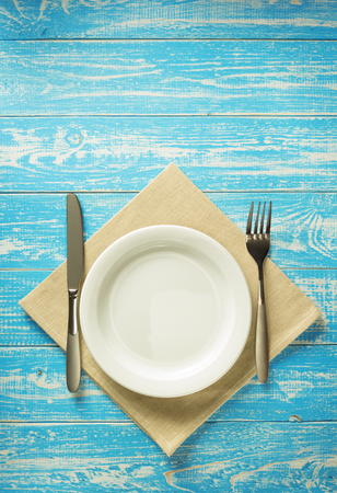 serving utensil: plate, knife and fork on rustic wooden background