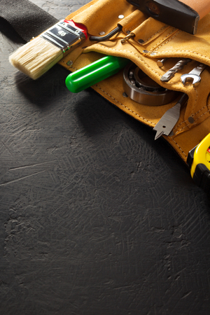 housebuilding: tools and instruments in belt on black background