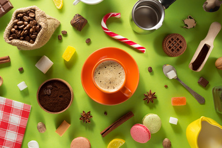cup of coffee and ingredients at colorful paper background