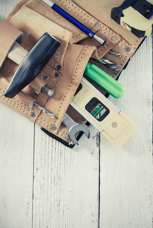 black leather texture: tools and instruments in belt on wooden background Stock Photo