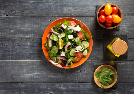 cucumbers: fresh greek salad in plate and ingredients on wooden table