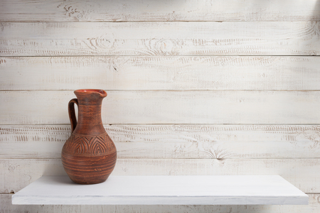 clay jug at shelf on white wooden plank background