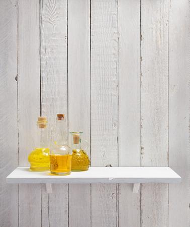 bottle of oil at shelf on wooden background