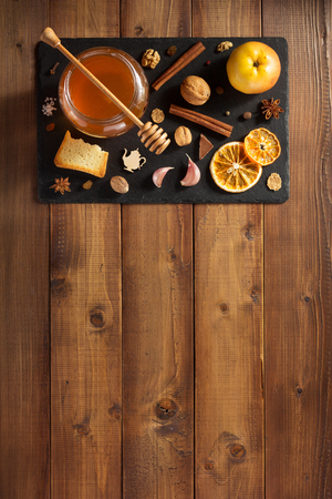 glass jar of honey on wooden background