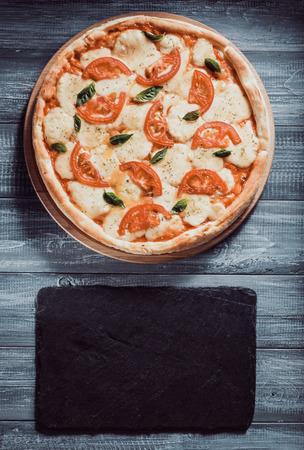 margarita pizza at wooden table Banco de Imagens