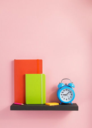 notepad and alarm clock on shelf at wall background surface