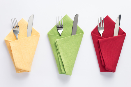 knife and fork in folded napkin at white background, top view