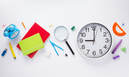 school accessories and wall clock at white background, top view
