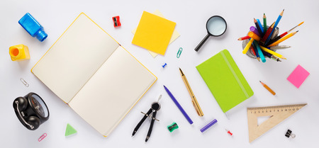school accessories and open notebook or book with empty pages at white background, top view