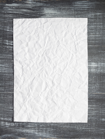 Empty white wrinkled paper at wooden Stock Photo