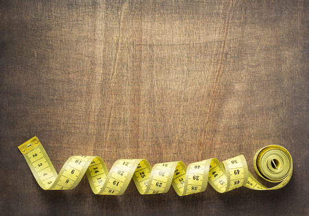 tape measure on wooden table background, top view
