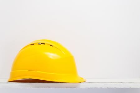 casque de construction sur une étagère en bois au mur de texture de fond blanc Banque d'images