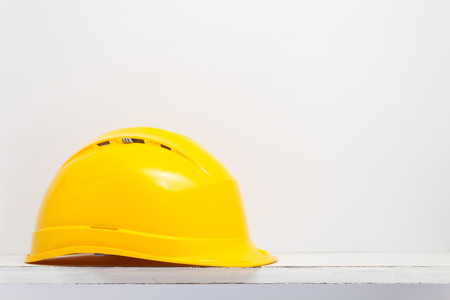 construction helmet on wooden shelf at white background texture wall