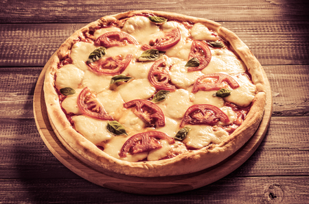 fresh margarita pizza at wooden table Imagens
