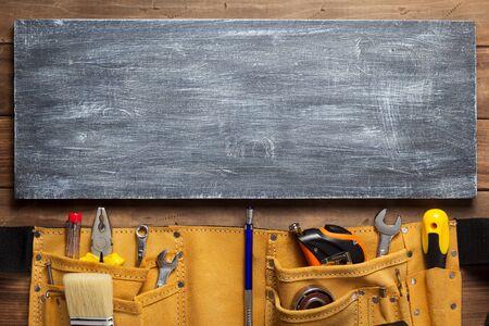 Instrumente im Werkzeuggürtel am Holztischoberflächenhintergrund Standard-Bild