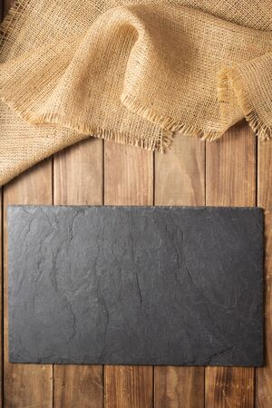 slate stone sign board at wooden plank, background texture surface