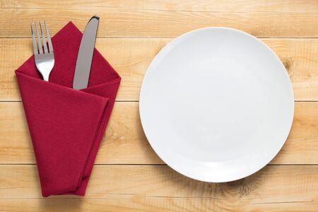 Teller, Messer und Gabel am rustikalen Holzbrett-Tischhintergrund, Draufsicht