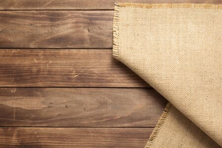 burlap hessian sacking on wooden background table, top view