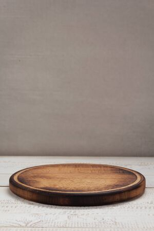 pizza cutting board at rustic wooden table in front plank background