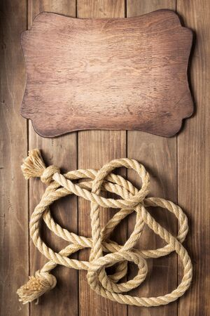 sign board and ship rope at wooden background texture, top veiw Reklamní fotografie