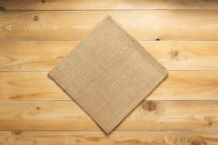 burlap hessian sacking cloth on wooden background table, top view