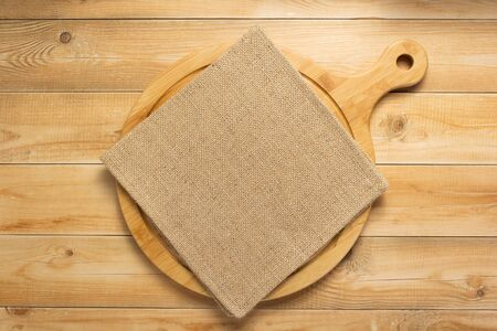 pizza cutting board and naplin at rustic wooden plank background, top view