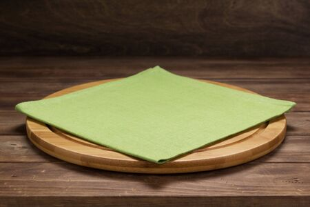pizza cutting and napkin tablecloth board at rustic wooden table, in front plank background Фото со стока