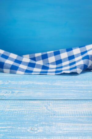 cloth napkin at blue rustic table in front, wooden plank board background