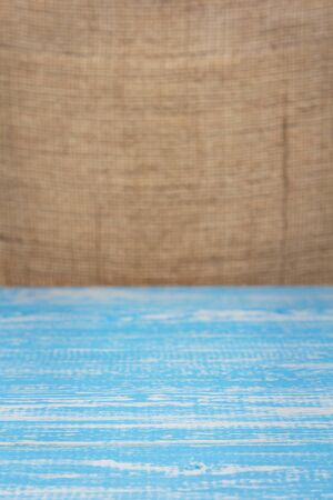 wooden board plank table and burlap hessian sacking background, table in front view