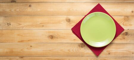 plate and napkin cloth at rustic wooden plank board table background, top view
