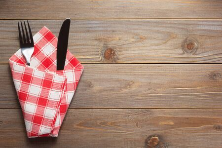 knife and fork in napkin at rustic wooden plank board table background, top view