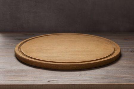Pizzaschneidebrett am rustikalen Holztisch im vorderen Plankenhintergrund Standard-Bild