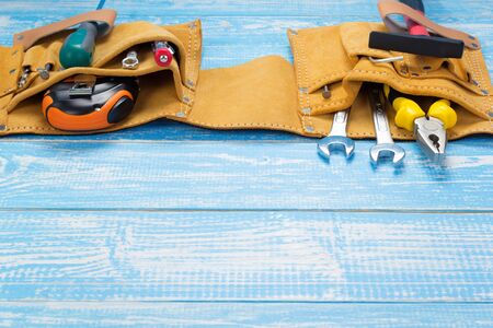 Tools and instruments in belt on wooden table in front, plank board Stock Photo