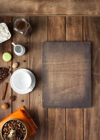 empty cup of coffee and beans on wooden background table, top view