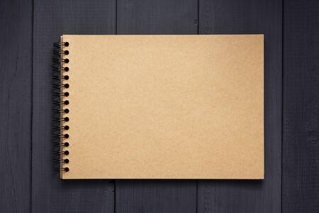cahier de papier à la table de surface de fond en bois noir, vue de dessus