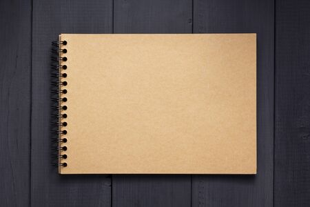 paper notebook at black wooden background surface table, top view