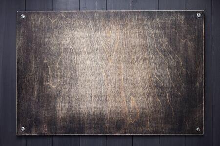 Placa de madera en la superficie de textura de fondo negro con tornillos