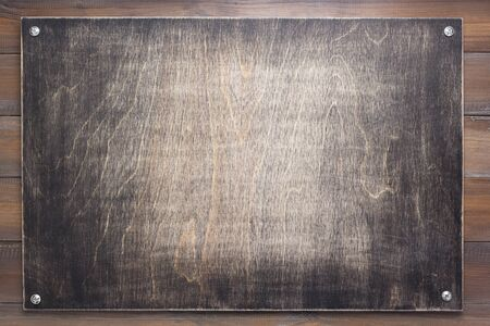 Typenschild auf hölzerner Hintergrundtextur, auf Bretterwand Standard-Bild