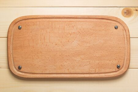 cutting board at rustic wooden plank background, top view
