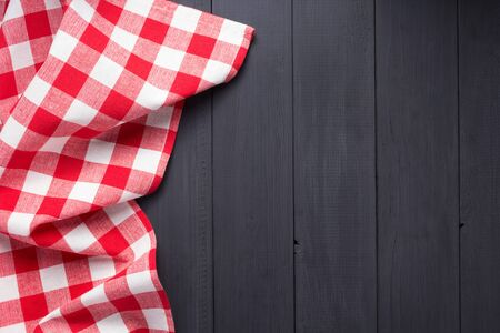 cloth napkin or tablecloth checked at rustic wooden plank board table background, top view